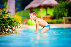 Cute wet kid, boy enjoying vacation in tropical pool Royalty Free Stock Photos