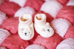 Cute white baby booties on red blanket. Pregnancy concept Royalty Free Stock Photography