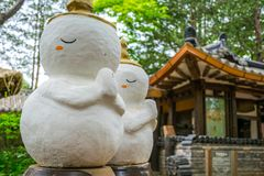 The cute white dolls with tradition house in background at Nami Island. stock photos