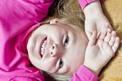 Cute white girl with blond hair. Cute smiling girl with blond hair in pink stock photography