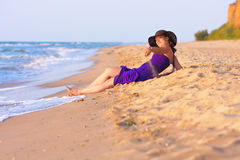 Cute white girl laying on sand at the beach Stock Images