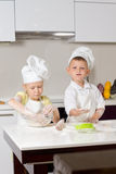Cute White Little Chefs Baking in Kitchen. Cute White Little Chefs Baking on White Wooden Table in the Kitchen royalty free stock photo