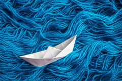Cute white of origami boat floating on the waves of the yarn. Cute white of origami boat floats on the sea waves of woolen yarn Royalty Free Stock Images