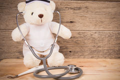 Cute white tebby bear wear nurse with stethoscope and thermometer on wooden background ,vintage tone stock images