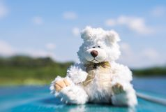 Cute white teddy bear on board a motor boat. Active summer holidays. Cute white teddy bear on summer vacation. Toy on board a promenade on the lake with water stock photography