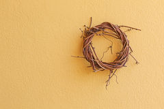 Cute wicker wooden wreath made of dried branch hanging on yellow royalty free stock photos