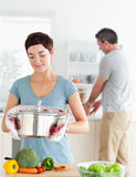 Cute wife holding a pot while her husband Royalty Free Stock Photography