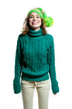 Cute winter girl. Young funny cute winter girl wearing green warm woolen knitted sweater, yellow green bright hat with pom pon, colorful makeup, looking happily Royalty Free Stock Photography