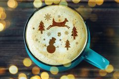 Cute winter pattern in a Cup on the milk foam cappuccino coffee. Merry Christmas. Cute winter pattern in a Cup on the milk foam cappuccino coffee. Christmas mood royalty free stock image