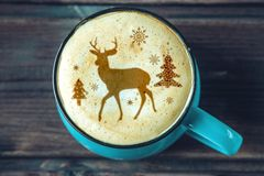 Cute winter pattern in a Cup on the milk foam cappuccino coffee. Merry Christmas. Cute winter pattern in a Cup on the milk foam cappuccino coffee. Christmas mood royalty free stock photography