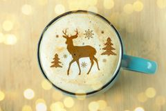 Cute winter pattern in a Cup on the milk foam cappuccino coffee. Merry Christmas. Cute winter pattern in a Cup on the milk foam cappuccino coffee. Christmas mood royalty free stock photos