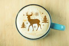 Cute winter pattern in a Cup on the milk foam cappuccino coffee. Merry Christmas. Cute winter pattern in a Cup on the milk foam cappuccino coffee. Christmas mood royalty free stock photo