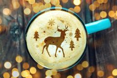 Cute winter pattern in a Cup on the milk foam cappuccino coffee. Merry Christmas. Cute winter pattern in a Cup on the milk foam cappuccino coffee. Christmas mood stock images