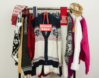 Cute winter sweaters displayed on hangers with a big sale sign. Stock Image