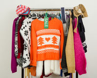 Cute winter sweaters displayed on hangers with a big sale sign. Royalty Free Stock Photography