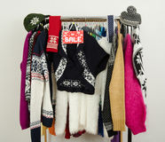 Cute winter sweaters displayed on hangers with a big sale sign. Stock Photos