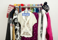 Cute winter sweaters displayed on hangers with a big sale sign. Royalty Free Stock Photos