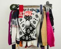 Cute winter sweaters displayed on hangers with a big sale sign. Royalty Free Stock Image