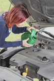 Cute woman is adding oil in the car Stock Image