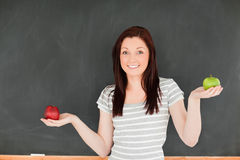 Cute woman with an apple on each hand Royalty Free Stock Images