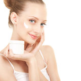 Cute woman applying cream to face Stock Images