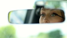 Cute woman applying mascara in car rearview mirror stock footage