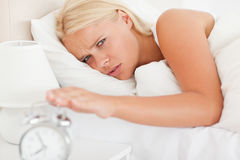 Cute woman awaken by an alarmclock Royalty Free Stock Images