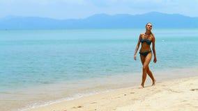 Cute woman in bikini walking on the beach Royalty Free Stock Photography