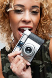 Cute Woman Biting a Retro Camera royalty free stock photos