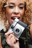 Cute Woman Biting a Retro Camera Royalty Free Stock Photos