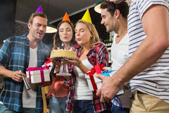 Cute woman blowing her birthday candles with a group of friends Stock Photo