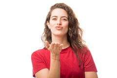 Cute woman blowing a kiss. Beautiful young woman blowing a kiss while standing on white background Stock Images