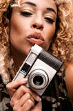 Cute Woman Blowing a Kiss While Holding a Retro Camera Royalty Free Stock Photos