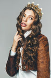 Cute woman in brown leather jacket and golden crown. In studio Royalty Free Stock Image