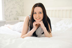 Cute woman brunette smiling on the bed Stock Images