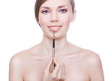 Cute woman with brush on lips Stock Image