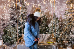Cute woman buttoned up her blue down jacket and standing near sw. Ing with a blanket under the flashlights in a snow-covered park, wearing warm woolen knitted Royalty Free Stock Images