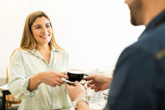 Cute woman buying a cup of coffee. Portrait of a gorgeous young women buying a cup of coffee at a cafe and smiling Stock Images