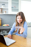 Cute woman buying online using laptop and card Stock Photography