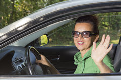 Cute woman in the car waving hello Royalty Free Stock Photography