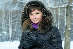 Cute woman with cellphone in frosty day Royalty Free Stock Photo