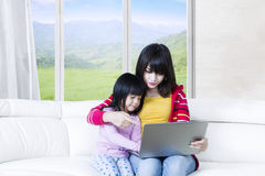 Cute woman and child with laptop Stock Image