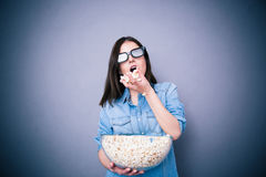 Cute woman in cinema glasses eating popcorn Stock Image
