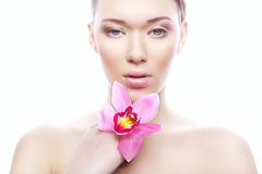 Cute woman with clean skin and pink flower Stock Image