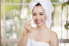 Cute woman cleaning her face Stock Photography