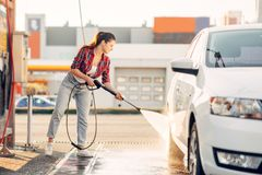 Cute woman cleans car wheels with water gun. Cute woman cleans car wheels with high pressure water gun. Young lady on self-service automobile wash. Outdoor stock images