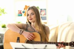 Cute Woman Composer Working on Music Composition. Woman Playing Guitar while Sitting on Couch at Home. Blonde Looking at Camera. Beautiful Caucasian Girl royalty free stock image
