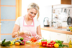 Cute woman cuts paprika for salad. In kitchen Royalty Free Stock Image