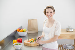 Cute woman cutting vegetables standing in her kitchen Stock Photos