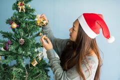 Cute woman decorate bells on xmas tree. Asian Chinese happy woman with santa claus hat decorate golden bells on Xmas tree. Attractive cute girl celebrate stock photos